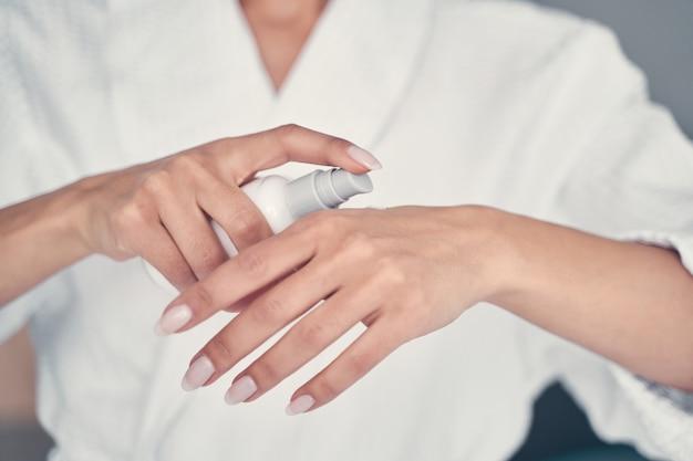 Foto recortada de uma jovem mulher branca em um roupão de banho aplicando um creme hidratante para as mãos