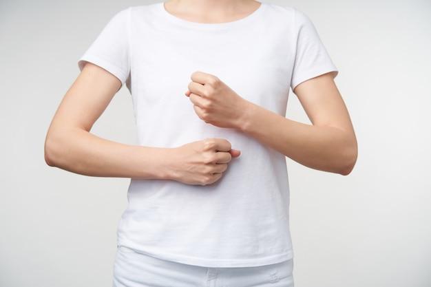 Foto recortada de uma jovem mulher com roupas casuais, mantendo um punho acima do outro, enquanto significa trabalhador da palavra na linguagem de sinais, isolado sobre fundo branco