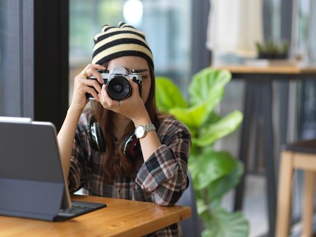 Foto recortada de uma jovem mulher usando uma câmera enquanto trabalha em um espaço de trabalho confortável