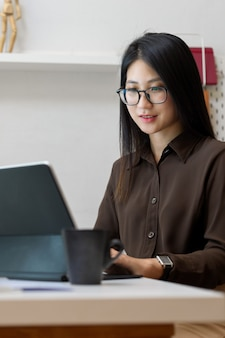 Foto recortada de uma jovem trabalhadora trabalhando em um tablet digital em uma confortável sala de escritório