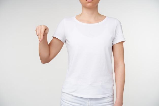 Foto recortada de uma jovem vestida com uma camiseta branca aparecendo com dois dedos enquanto aprende a linguagem dos surdos, sendo isolada sobre um fundo branco