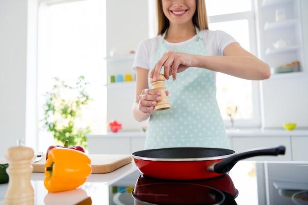Foto recortada de uma linda dona de casa com as mãos segurando sal adicionando ingredientes da frigideira cozinhando a preparação do jantar saboroso reunião familiar reunião com luz branca cozinha dentro de casa