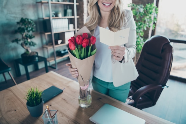 Foto recortada de uma linda mulher de negócios segurando pequenos buquê de tulipas