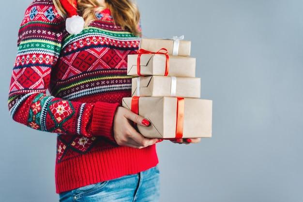 Foto recortada de uma menina loira com unhas vermelhas esmaltadas segurando um monte de caixas de presente embrulhadas em papel artesanal e decoradas com fita de cetim vermelha