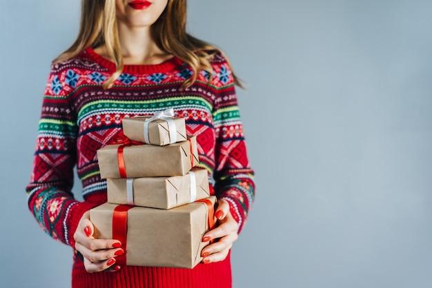 Foto recortada de uma menina loira sorridente com lábios vermelhos e unhas polidas segurando um monte de caixas de presente embrulhadas em papel artesanal e decoradas com fita de cetim vermelha