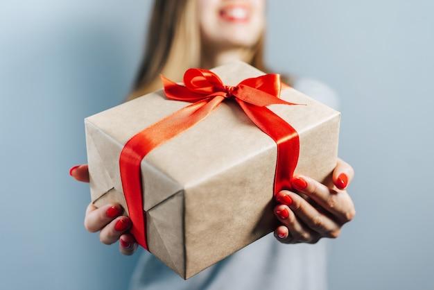 Foto recortada de uma menina loira sorridente com lábios vermelhos e unhas polidas segurando uma caixa de presente embrulhada em papel artesanal e decorada com fita de cetim vermelha