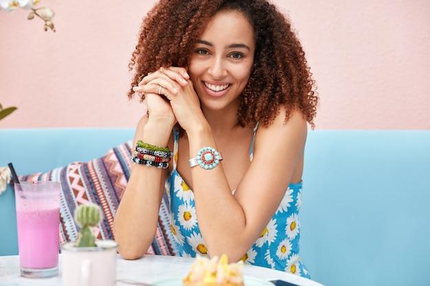 Foto recortada de uma mulher afro-americana bem parecida e relaxada que passa o tempo de lazer com amigos em um café, bebe milk-shake de frutas frescas