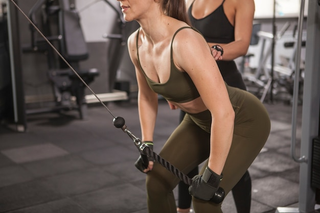 Foto recortada de uma mulher atlética fazendo exercícios para os músculos das costas na academia com o personal trainer