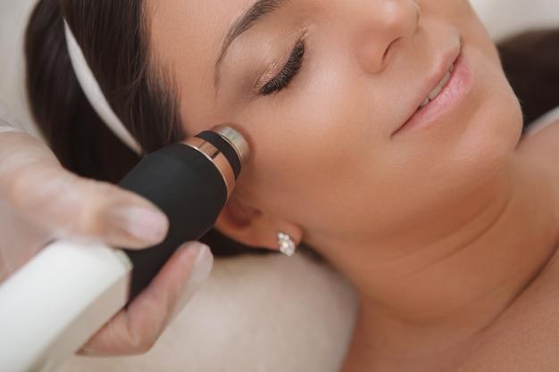 Foto recortada de uma mulher atraente desfrutando de um tratamento facial de cosmetologia de hardware em uma clínica de beleza