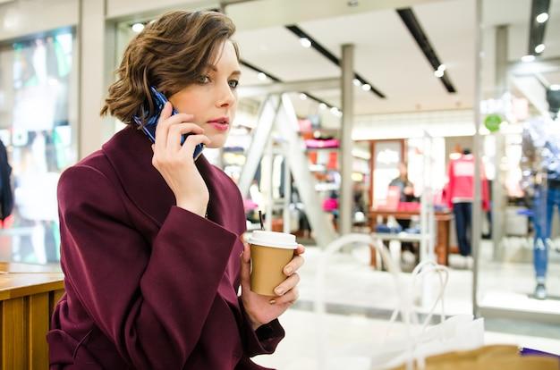 Foto recortada de uma mulher bonita. compras no shopping. mulher atraente sorridente no casaco roxo com café para ir e telefone