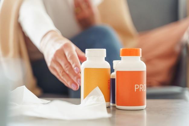 Foto recortada de uma mulher caucasiana pegando um frasco de comprimidos na mesa