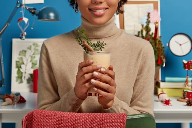 Foto recortada de uma mulher com um suéter marrom segurando uma saborosa bebida tradicional de natal cheia de canela e abeto