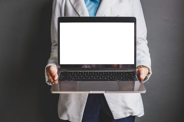 Foto recortada de uma mulher de negócios segurando um laptop com uma tela preta e branca para simulação de