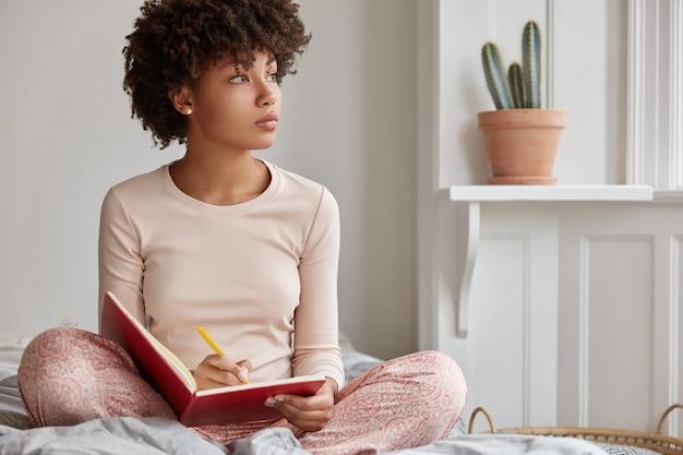 Foto recortada de uma mulher de pele escura sentada com as pernas cruzadas, usando pijama
