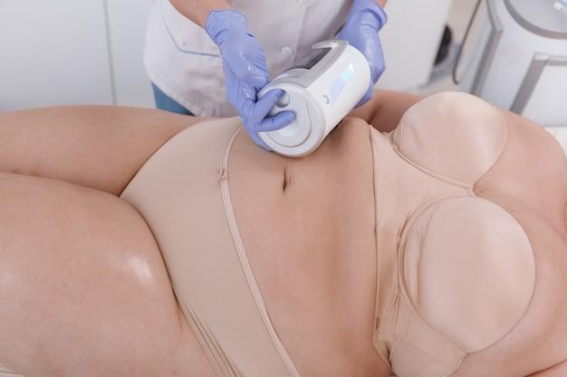Foto recortada de uma mulher de tamanho grande recebendo massagem de emagrecimento feita por cosmetologista