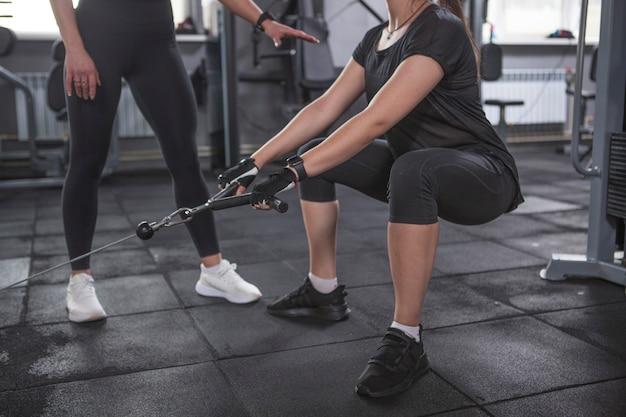 Foto recortada de uma mulher fazendo exercícios de glúteos na academia com um personal trainer