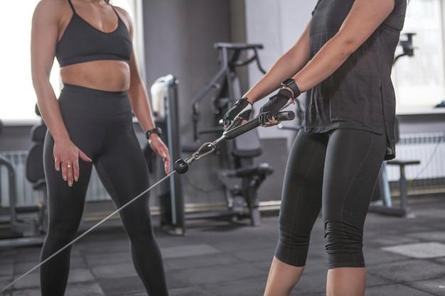 Foto recortada de uma mulher irreconhecível fazendo agachamentos na academia com o personal trainer