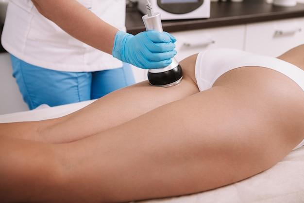 Foto recortada de uma mulher recebendo tratamento de levantamento de rf na parte de trás das pernas por uma esteticista profissional