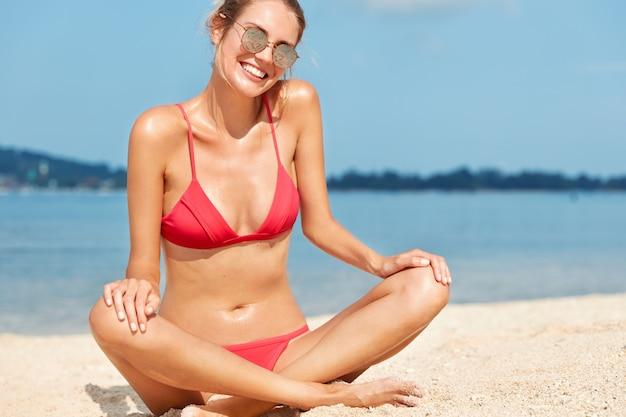 Foto recortada de uma mulher relaxada e despreocupada com uma expressão feliz, senta-se na areia quente perto do oceano, toma banho de sol sozinho, desfruta de uma atmosfera calma e mantém as pernas cruzadas. pessoas, local do resort e horário de verão
