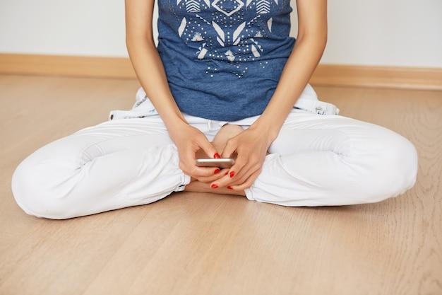 Foto recortada de uma mulher sentada em posição de lótus no chão de madeira enquanto digita a mensagem de texto