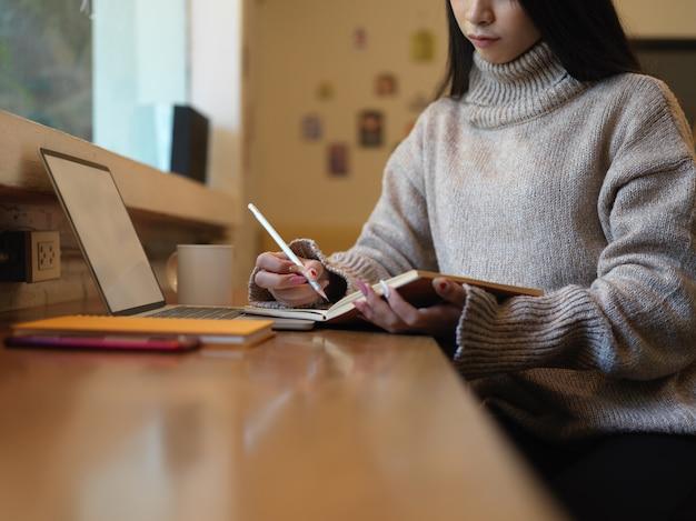 Foto recortada de uma mulher tomando nota enquanto trabalha com uma simulação de laptop no balcão do café