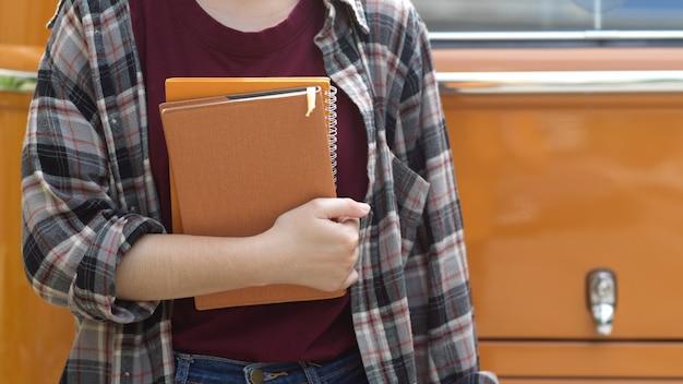 Foto recortada de uma trabalhadora segurando cadernos em frente à van