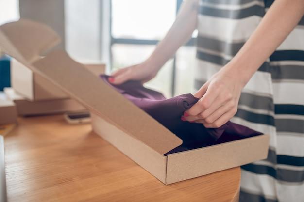 Foto recortada de uma vendedora ocupada colocando uma peça de roupa em uma caixa de papelão