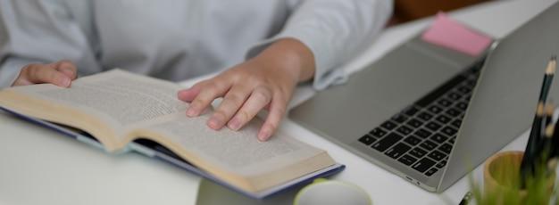 Foto recortada de universitária procurando informações no livro