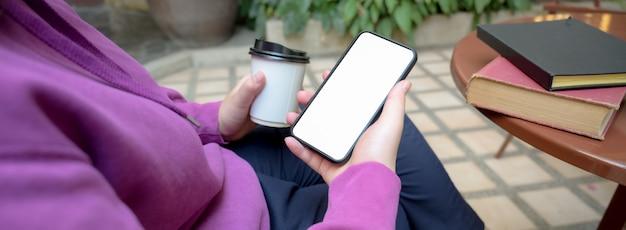 Foto recortada de universitária relaxante com smartphone e bebendo café quente