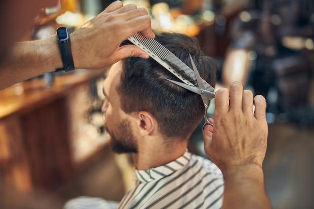 Foto recortada de visão lateral de um homem moreno fazendo um novo penteado em uma barbearia