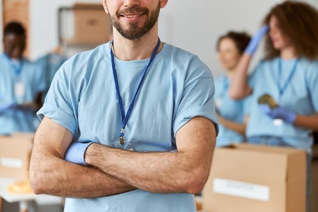 Foto recortada de voluntário do sexo masculino caucasiano de uniforme e luvas de proteção em pé com os braços cruzados