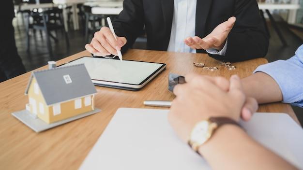 Foto recortada do agente de empréstimo da casa usando o tablet de tela em branco ao apresentar ao cliente