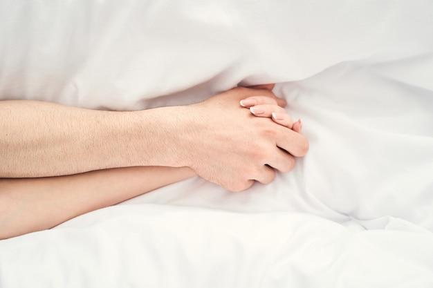 Foto recortada do apaixonado casal caucasiano recém-casado, segurando as mãos um do outro na cama