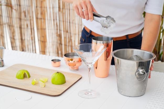 Foto recortada do barman colocando o cubo de gelo na coqueteleira,