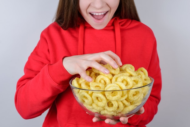 Foto recortada do close up de uma pessoa engraçada e animada, animada e alegre, com a boca aberta, uma pessoa adolescente pegando o prato cheio com a mão isolada na parede cinza