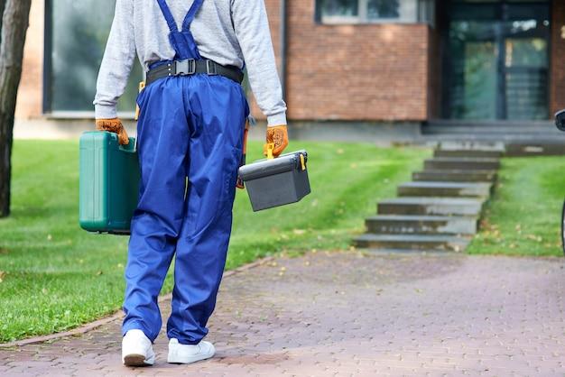Foto recortada do construtor carregando uma caixa de ferramentas no canteiro de obras