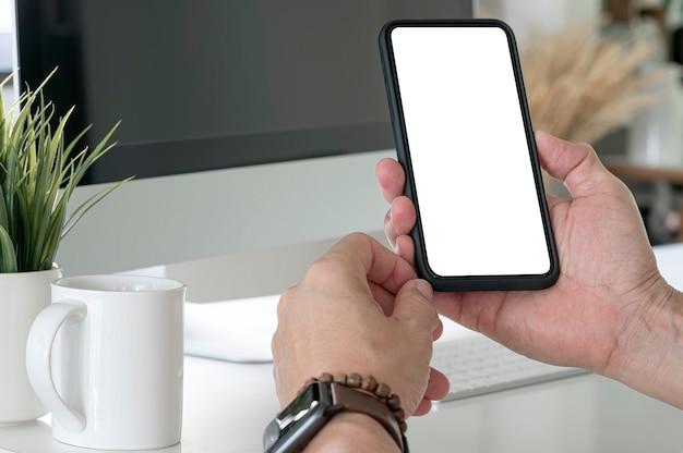 Foto recortada do empresário profissional segurando o smartphone de tela em branco enquanto está sentado na sala de um escritório moderno.
