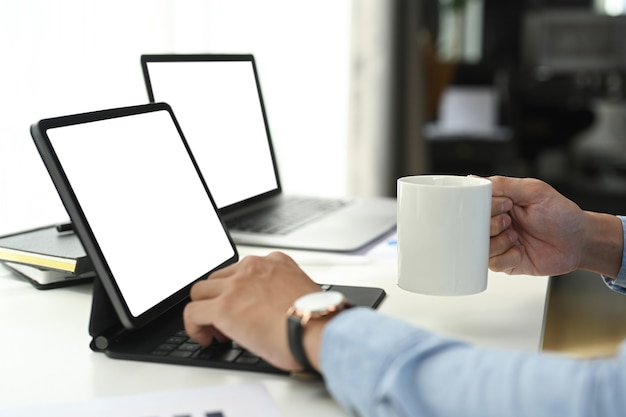 Foto recortada do empresário trabalhando no tablet do computador enquanto a mão segurando a xícara de café no escritório.