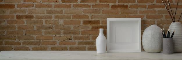Foto recortada do espaço de trabalho contemporâneo com moldura, vasos de cerâmica, artigos de papelaria e cópia espaço