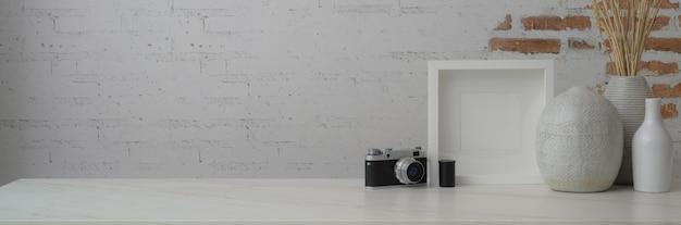 Foto recortada do espaço de trabalho contemporâneo com moldura, vasos de cerâmica, espaço para câmera e cópia