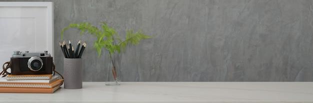 Foto recortada do espaço de trabalho da moda com câmera, livros, artigos de papelaria, planta com espaço de vaso e cópia