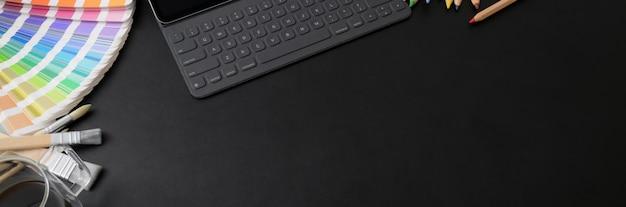 Foto recortada do espaço de trabalho de designer com teclado tablet, amostra colorida e espaço para cópia