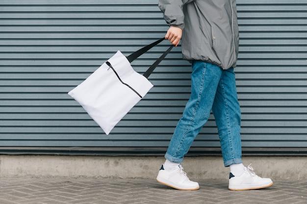 Foto recortada do fundo de um jovem em roupas elegantes, andando com uma bolsa ecológica branca na mão. eco amigável