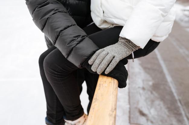 Foto recortada do jovem casal apaixonado, abraçando na pista de gelo