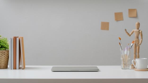Foto recortada do local de trabalho de design com laptop, xícara de café, ferramentas de pintura e decorações na mesa branca