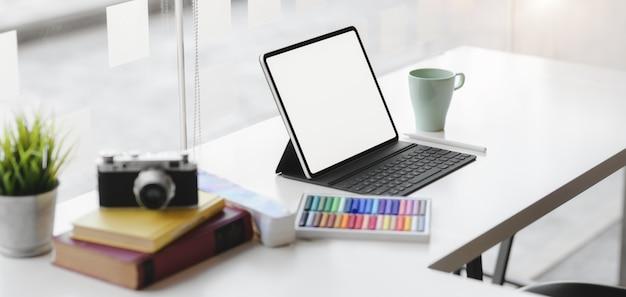 Foto recortada do local de trabalho do designer gráfico moderno com tablet digital de tela em branco, câmera e material de escritório