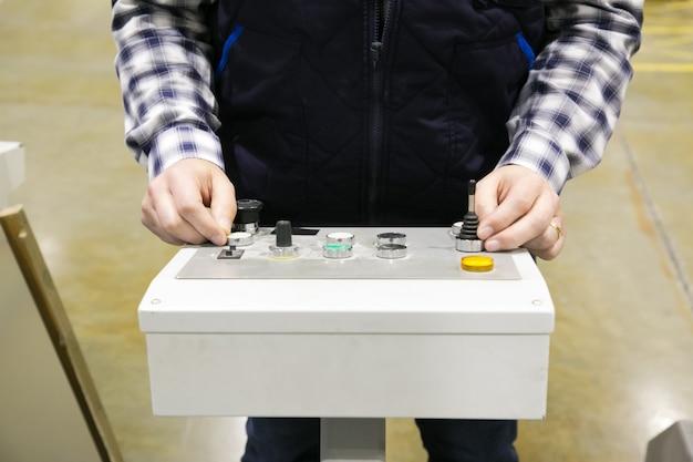 Foto recortada do operador de máquina da fábrica pressionando os botões