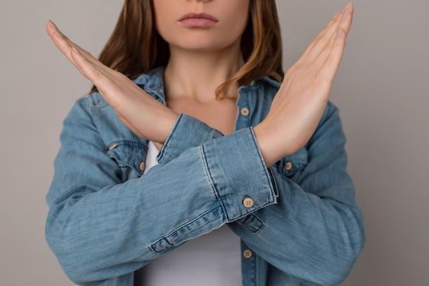 Foto recortada em close-up de uma mulher séria e estrita sem voz mostrando a demonstração de fazer o sinal da cruz com os braços, camisa jeans casual, isolada na parede cinza