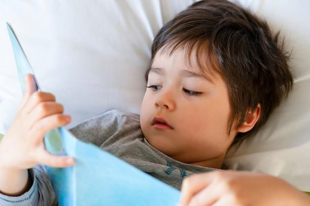 Foto recortada uma criança feliz encontra-se na cama lendo um livro, menino feliz criança lendo seu livro de histórias favorit antes de dormir, conceito de história de hora de dormir