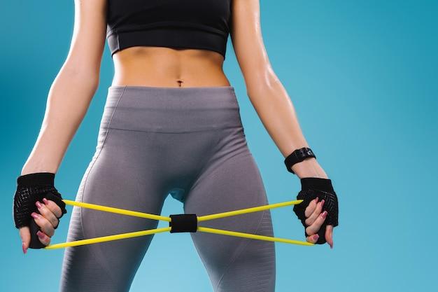 Foto recortada. uma figura feminina robusta em leggings e um top preto e braços com um elástico para